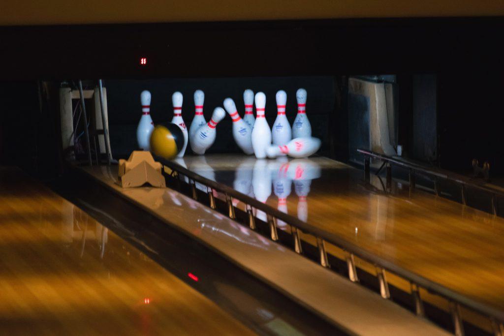 bowling ball hitting down pins at a bowling alley